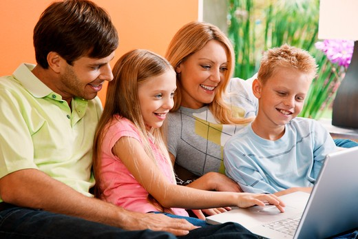 family relaxing together at home using laptop : Stock Photo