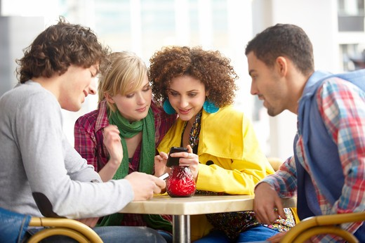 Stock Photo: 1491R-1165723 A group of four teenage friends in a cafe looking at their mobile phones