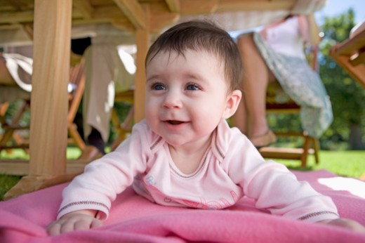 Stock Photo: 1491R-1165748 Baby lying on a blanket underneath a table outdoors