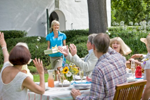 A female guest arriving with a gift at a summer garden party : Stock Photo