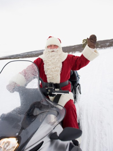 Stock Photo: 1491R-1165859 Santa Claus riding a Skidoo, waving
