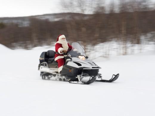 Santa Claus riding a Skidoo through the snow : Stock Photo