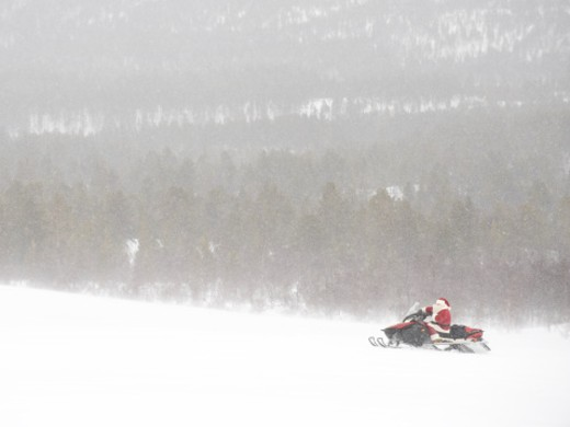 Santa Claus riding a Skidoo through the snow : Stock Photo