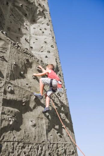 A young boy scaling a climbing wall : Stock Photo