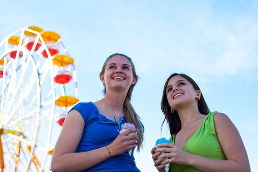 Stock Photo: 1491R-1166389 Teenagers eating snow cones by the ferris wheel at