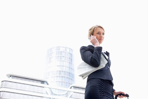 Stock Photo: 1491R-1167640 Low angle view of young businesswoman on cell phone outdoors