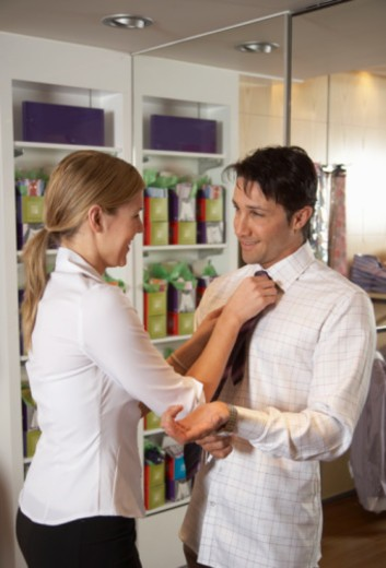 Young woman fixing tie for man in clothes store, smiling : Stock Photo