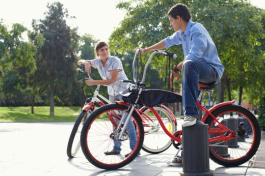 Teenage couple (13-17) sitting on bikes in park, smiling : Stock Photo