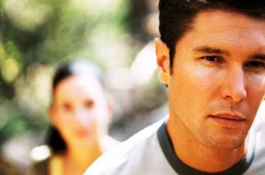 Close-up of a young man looking at camera with a young woman behind him : Stock Photo