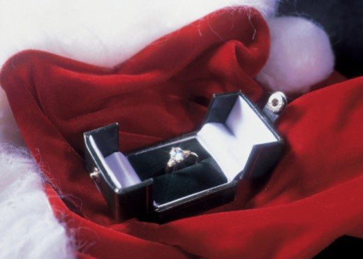 high angle of a solitaire ring in a box kept on red cloth and cotton : Stock Photo