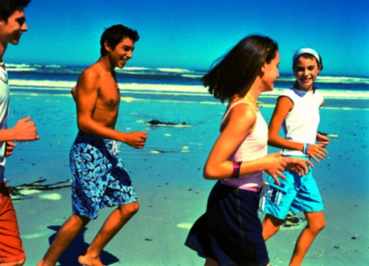 Stock Photo: 1491R-1168961 Group of teenagers (14-18) smiling running at the beach