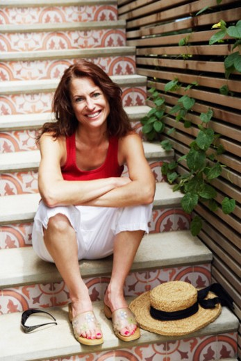 Portrait of a mature woman sitting on a staircase and smiling : Stock Photo