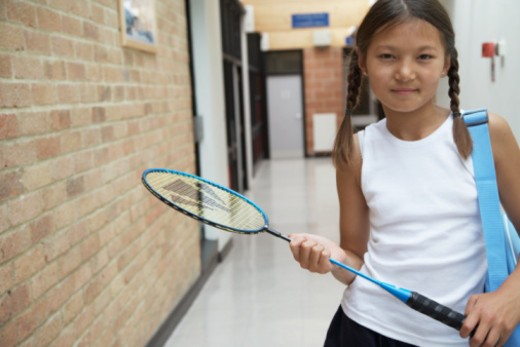 Stock Photo: 1491R-1169473 Girl (9-11) holding badminton racket in hallway