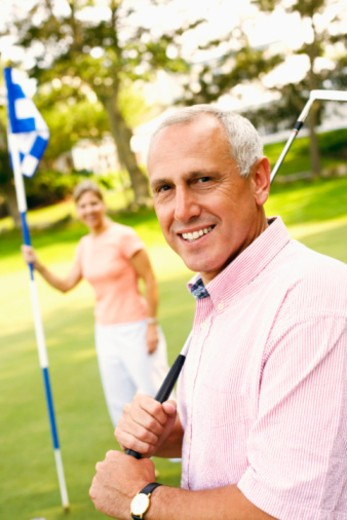Stock Photo: 1491R-1169818 Portrait of a mature man holding a golf club with a mature woman holding a golf flag in the background