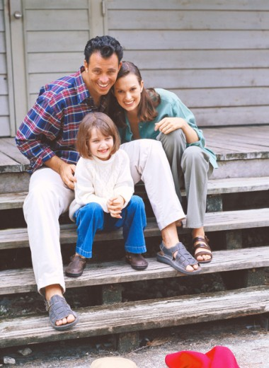 view of a mother and father sitting on steps with their daughter : Stock Photo