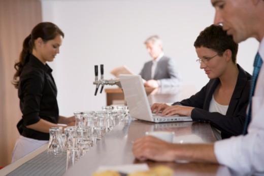 Businesswoman at bar using laptop : Stock Photo