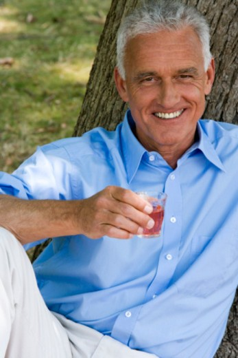 Portrait of happy mature man with drink outdoors : Stock Photo