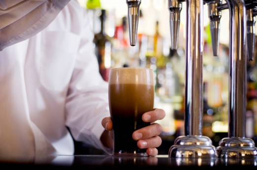 Stock Photo: 1491R-1170435 Barman pulling a pint of stout