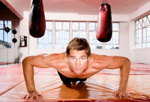 Boxer training at the gym, doing press ups : Stock Photo