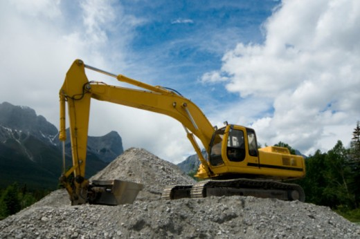 Stock Photo: 1491R-1170593 backhoe working against a mountain landscape.