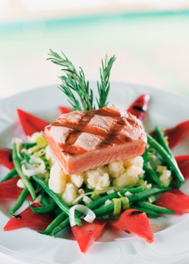 Detail of Grilled Salmon entree , on a bed of red bell peppers, green beans, onion, and potatoes  : Stock Photo