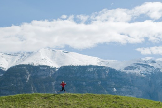 Stock Photo: 1491R-1170690 Young woman running in the Rockie Mountains.