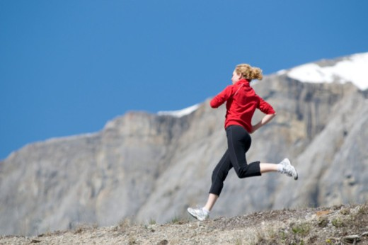 Young woman running in the Rockie Mountains. : Stock Photo