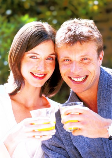 Stock Photo: 1491R-117133 portrait of a couple holding up glasses of orange juice