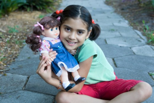 Stock Photo: 1491R-1171676 8 year old Hispanic girl poses with her doll.