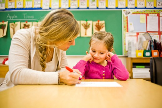 A teacher and her student working together in her classroom. : Stock Photo