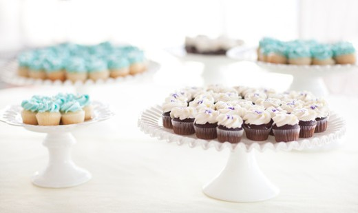 Three white cake plates with several cupcakes. Blue and white frosting top chocolate and vanilla cupcakes. : Stock Photo