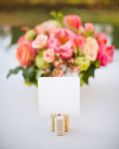 Place card in wine corks on a table outdoors with pink flowers out of focus. White paper card is blank. : Stock Photo