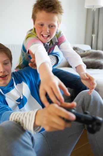 Stock Photo: 1491R-1172804 Teenage boys playing video game together at home
