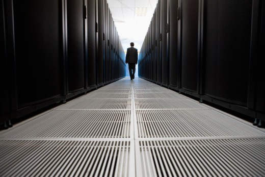Rear view of businessman walking in server room in Cape Town, South Africa : Stock Photo