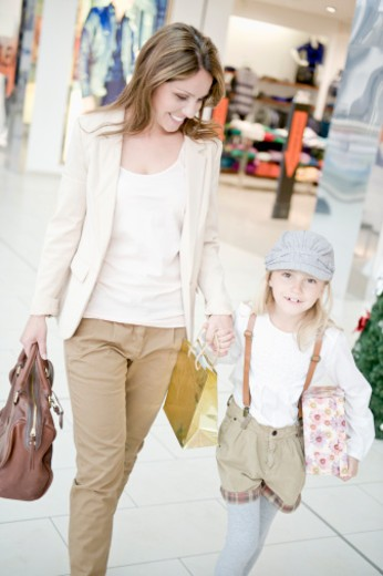 Mother and daughter walking together in shopping mall : Stock Photo