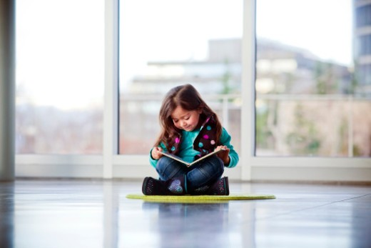 A young girl writing, reading and playing inside a museum. : Stock Photo