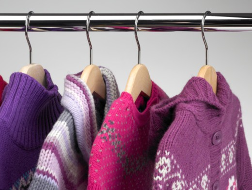 Dresses and cardigans hanging at a clothes shop. All garments are winter clothes and they are multicolored. Horizontal frame. : Stock Photo