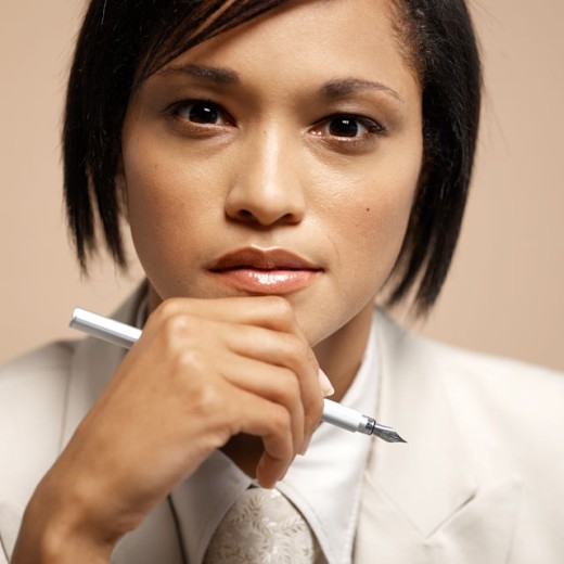 Stock Photo: 1491R-117407 Close-up of a young businesswoman holding a pen to her chin