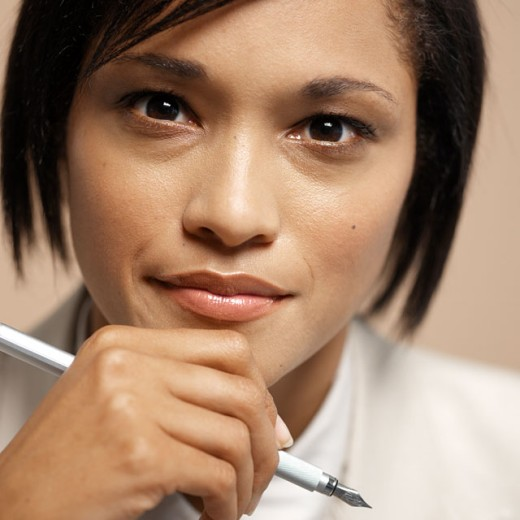 Close-up of a young businesswoman holding a pen to her chin : Stock Photo