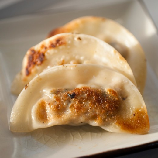 Stock Photo: 1491R-1174153 Close up of pot stickers. Small dumplings made of won ton skins filled with ground meat or shellfish, chopped water chestnuts, scallions and seasonings. Pot stickers are browned then simmered in broth. Often served as appetizers with dipping sauces.