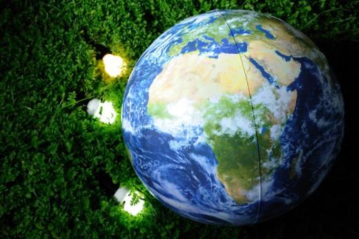 Energy saving light bulbs and inflatable earth ball on green grass. : Stock Photo