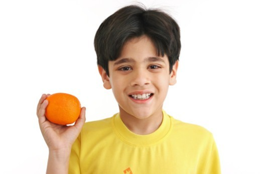 Stock Photo: 1491R-1175373 Portrait of a boy holding an orange