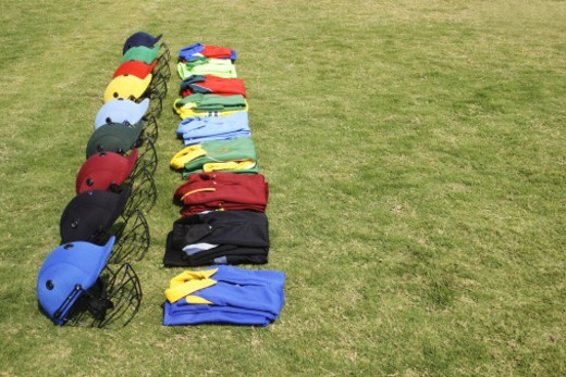 Stock Photo: 1491R-1175771 Cricket helmets and jerseys on the ground