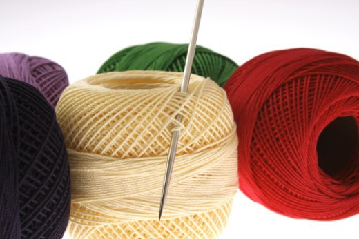 Close up of spools of coloured thread and a needle : Stock Photo