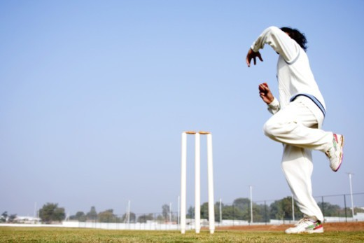 Low angle view of a bowler in action : Stock Photo