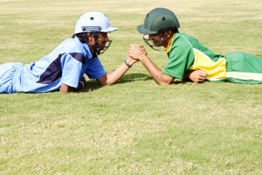 Stock Photo: 1491R-1179120 Cricket rivals engaged in arm wrestling