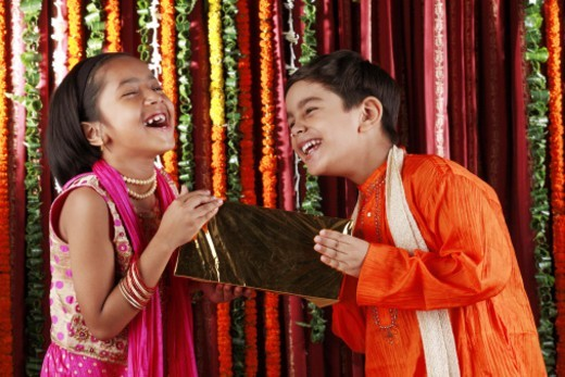 Stock Photo: 1491R-1179505 Boy and a girl holding a gift box