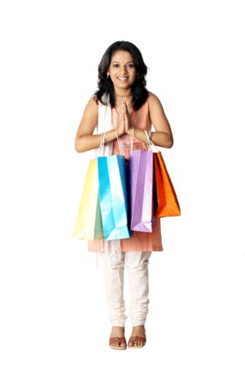 Woman with welcome gesture and shopping bags : Stock Photo