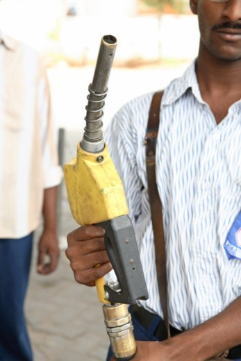 Stock Photo: 1491R-1180643 Person holding a petrol pump