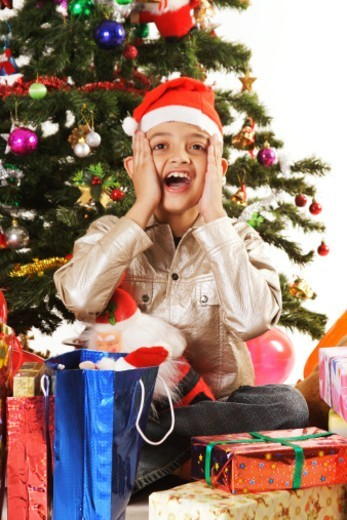 Portrait of a boy surrounded by gifts : Stock Photo